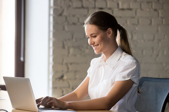 Smiling female working at laptop writing email