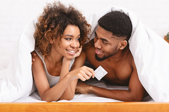 Young couple is smiling and holding condom