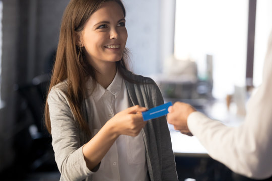 Businessman give business card to excited female employee
