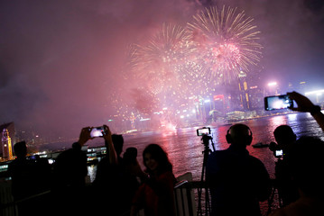 People take pictures as fireworks explode over Victoria Harbour to celebrate the Lunar New Year in Hong Kong