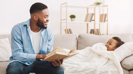 African-american father reading book to daughter on sofa