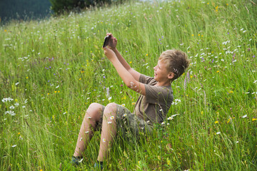 White handsome young kid taking selfie sitting at beautiful scenic meadow at countryside. Horizontal color photography.