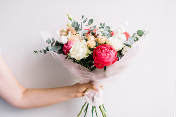 Very nice young woman's hand holding beautiful blossoming bouquet of fresh peony, roses, mattiola, eucalyptus, eustoma flowers in white and vivid red colors on the grey wall background