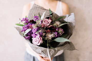 Very nice young woman holding beautiful blossoming bouquet of fresh roses, mattiola, carnations, eucalyptus flowers in purple color on the grey wall background
