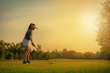Sport Healthy. Asian sporty woman golf player doing golf swing tee off on the green sunset evening time, she presumably does exercise. Healthy and Lifestyle Concept..