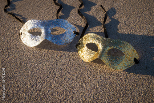 Sparkling gold and silver carnival masks resting on smooth