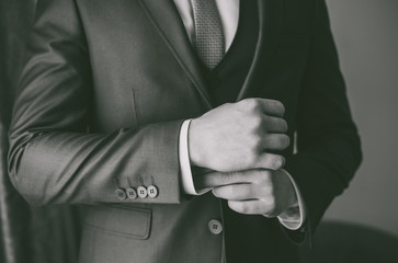 Closeup view of adult man getting dressed to official formal event. Man wearing white shirt, vest, jacket and necktie. Black and white photography.