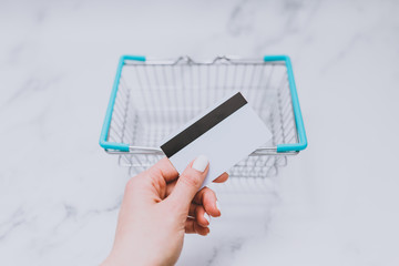 woman's hand holding payment card in front of empty shopping basket