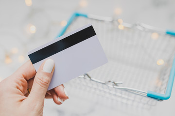 woman's hand holding payment card and empty shopping basket