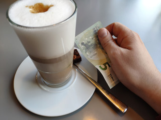 Cafe Latte and hand holding money