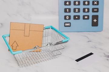 mini cardboard delivery parcel box into shopping basket with payment card and huge calculator in the background