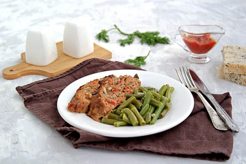 A meatloaf with mushrooms and red sweet pepper on a white plate with a garnish of fried green beans. Selective focus.