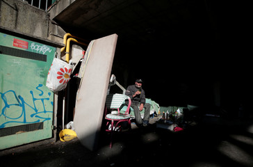 A French homeless man, Patrick Rubunelli, sits with his belongings under an overpass in Nice