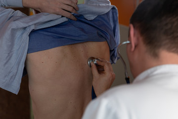The doctor is using stethoscope for auscultation