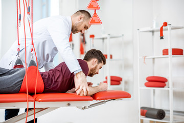 Senior physiotherapist doing treatment to a man with spine problems with suspension medical equipment at the rehabilitation clinic
