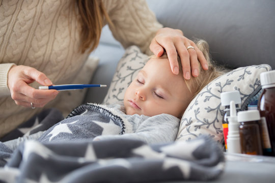 Sick child, toddler boy lying in bed with a fever, resting at home