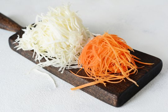 Slicing Fresh cabbage and carrots on a wooden board on a light background. Vegetables for ferment, for long fermentation. Assortment of fresh vegetables. Healthy food conception. Top view,shredded