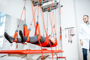 Man hanging on the suspension medical equipment during the spine treatment at the rehabilitation hospital