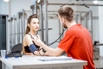 Man as a rehab in red uniform measuring pressure to a young woman sitting at the rehabilitation gym