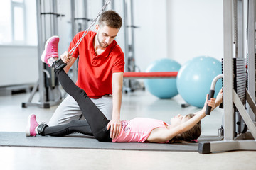 Young girl exercising on the decompression simulators with trainer during the spine treatment at the rehabilitation gym