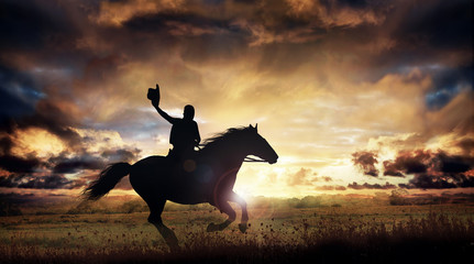 A silhouette of a cowboy and horse at sunset Wall mural