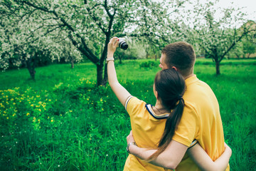 Young couple in love taking selfie in green blooming apple tree in countryside garden using small digital camera. Back view of young guy and girl isolated on green trees and grass background.