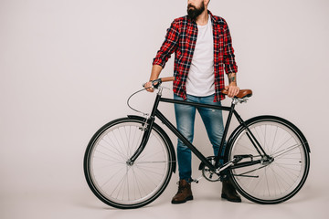 cropped view of man in checkered shirt posing with bicycle on grey