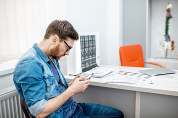 Man using smartphone sitting hunched down having scoliosis in the office of therapist at the clinic