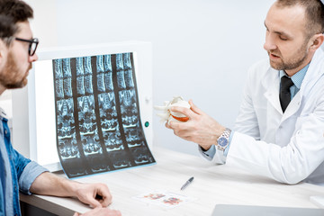Man during the medical consultation with senior therapist looking on the vertebral model at the office