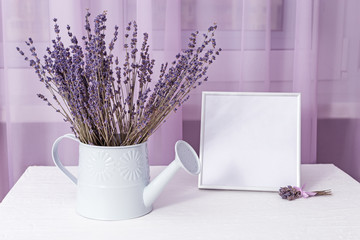 Bouquet of dry lavender in watering can with picture frame (mock-up) about window on white table. Soft focus.