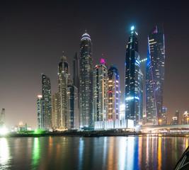 Dubai, United Arab Emirates - October, 2018: Colorful evening on canal and promenade in Dubai Marina, United Arab Emirates