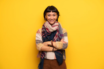 Young hippie woman over yellow wall keeping the arms crossed in frontal position