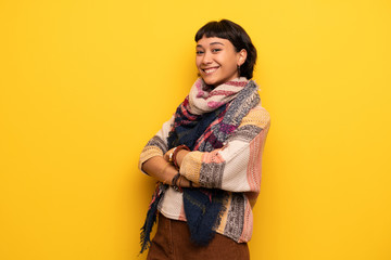 Young hippie woman over yellow wall keeping the arms crossed while smiling