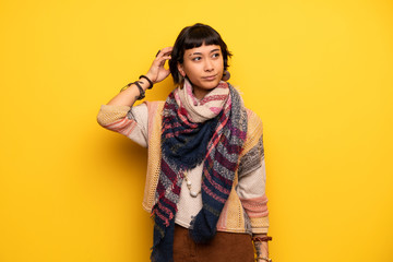 Young hippie woman over yellow wall having doubts while scratching head