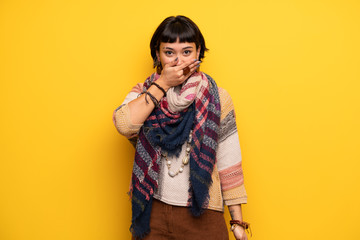 Young hippie woman over yellow wall covering mouth with hands for saying something inappropriate