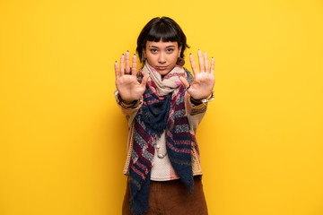 Young hippie woman over yellow wall making stop gesture for disappointed with an opinion