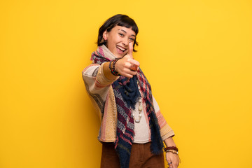Young hippie woman over yellow wall giving a thumbs up gesture because something good has happened