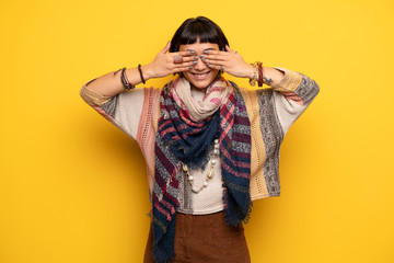 Young hippie woman over yellow wall covering eyes by hands. Surprised to see what is ahead