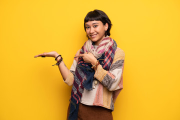 Young hippie woman over yellow wall holding copyspace imaginary on the palm to insert an ad