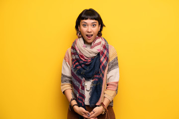 Young hippie woman over yellow wall with surprise and shocked facial expression