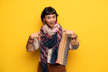 Young hippie woman over yellow wall with surprise facial expression