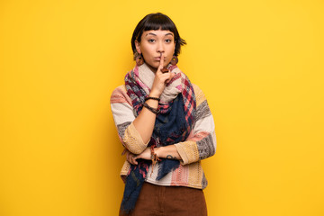 Young hippie woman over yellow wall showing a sign of silence gesture putting finger in mouth