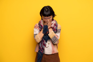 Young hippie woman over yellow wall with tired and sick expression