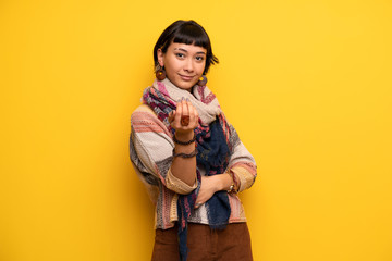 Young hippie woman over yellow wall inviting to come with hand. Happy that you came