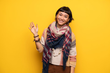 Young hippie woman over yellow wall saluting with hand with happy expression