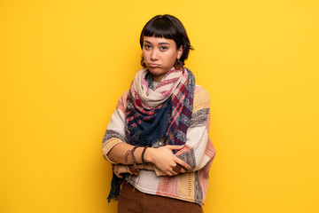 Young hippie woman over yellow wall with sad and depressed expression