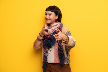 Young hippie woman over yellow wall pointing to the front and smiling
