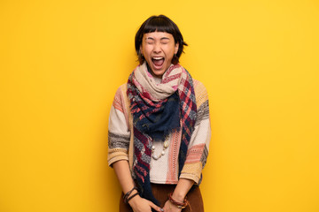 Young hippie woman over yellow wall shouting to the front with mouth wide open