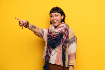 Young hippie woman over yellow wall pointing away