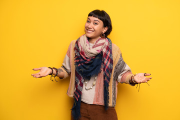 Young hippie woman over yellow wall smiling